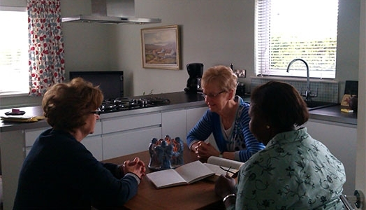 A group praying around a kitchen table